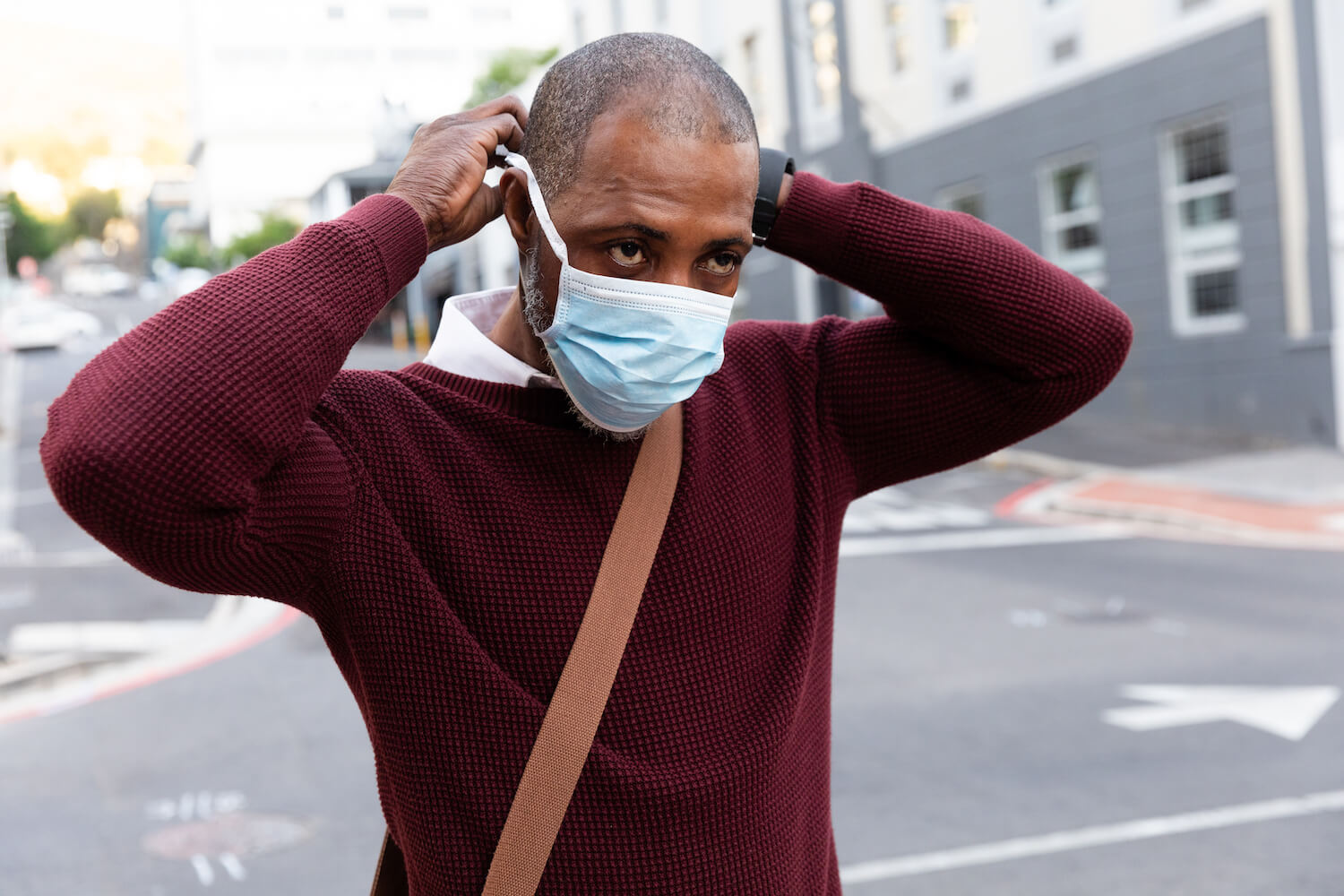 Man putting on face mask because of COVID-19 and the law