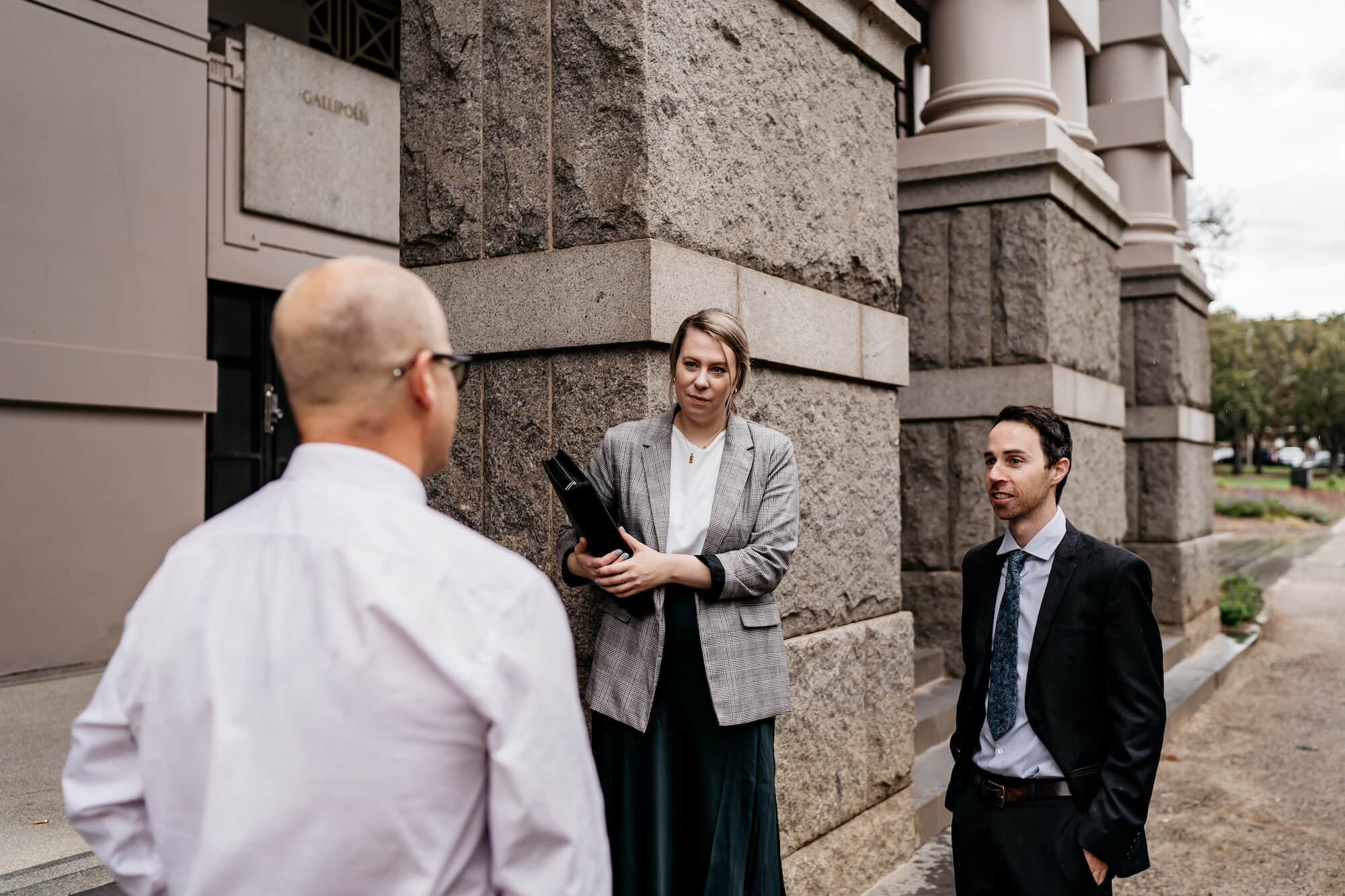 BCLS lawyers in front of stone building, discussing how to help with Centrelink issues